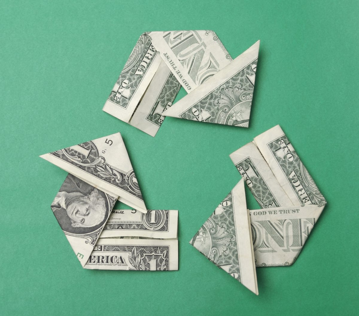 Recycling symbol made from dollar bills folded into arrows