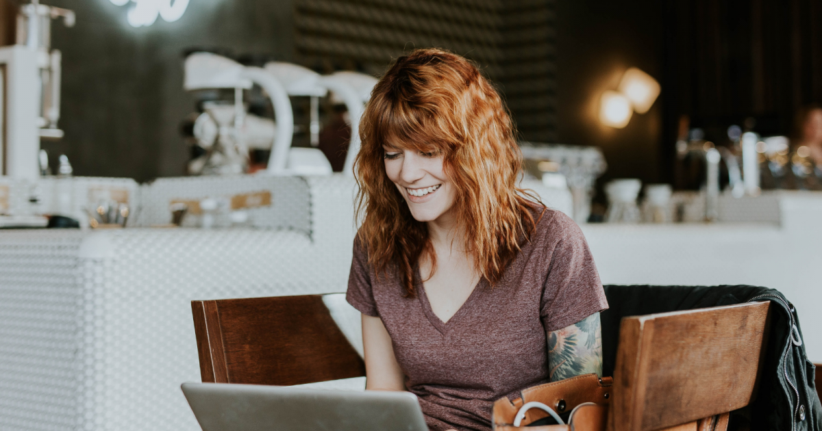 Woman smiling into computer.