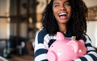 Woman smiling while holding a piggy bank