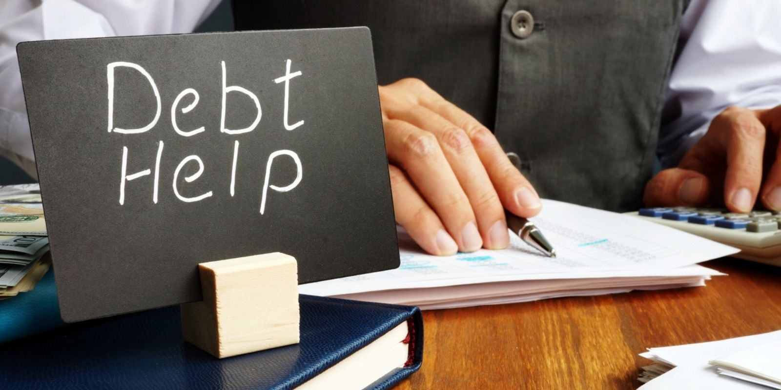 sign saying debt help and man writing